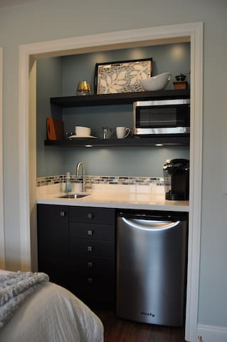 Kitchenette with microwave, bar sink, Keurig, and bar fridge.