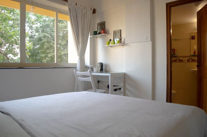 Queen size bed with study desk and attached private toilet and bath
