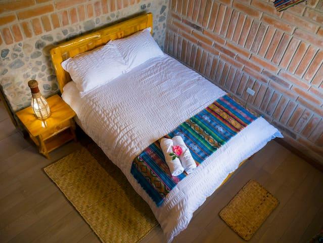 La habitación Allpa o Tierra , cuenta con una cama rustica tamaño doble para parejas  , el colchón es ortopédico y Las alomadas han sido elegidas para su descanso placentero . Ademas cuenta con una mesa y silla de madera rustica.