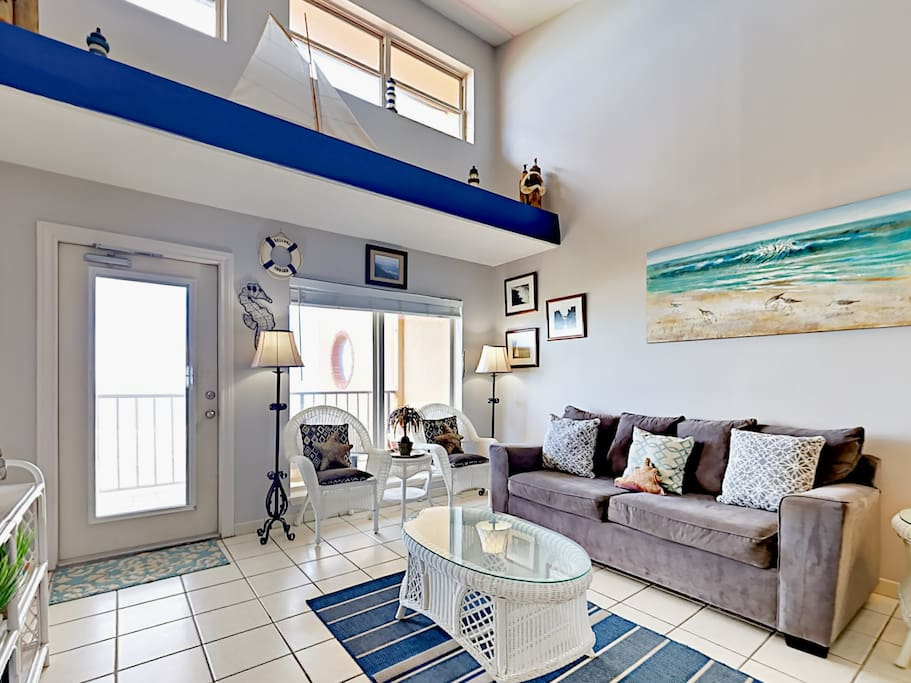 The living room seats 7 and offers balcony access with views of the Gulf of Mexico.