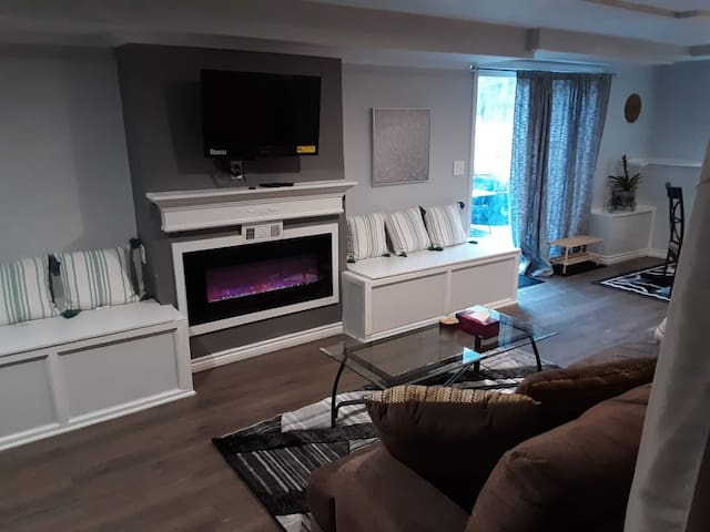 Living room area with fireplace, TV, couch. TV is equipped with Roku for streaming services.