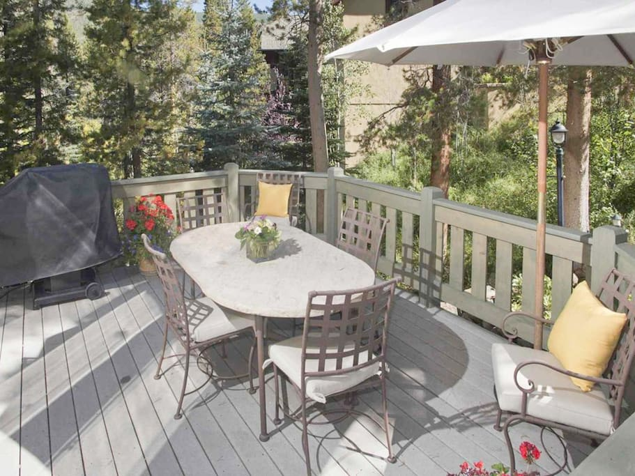 A gas grill and 4-person dining table await on the sunny deck.