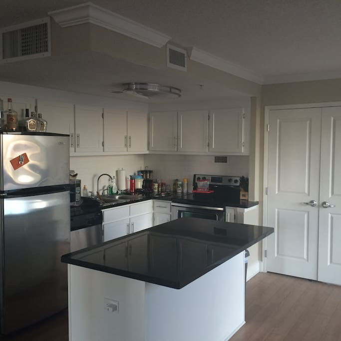 Kitchen with stainless steel fridge and oven/stove, and microwave. Granite counters with a granite island