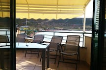 Pogled iz dnevne sobe na terasu sa tendom i na plazu Planjka