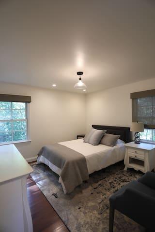 Master bedroom with queen bed, dresser, nightstands, closet and private bathroom.