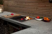 Outdoor kitchen with formed concrete top has built in Gas BBQ which is ready to cook on as soon as its lit.