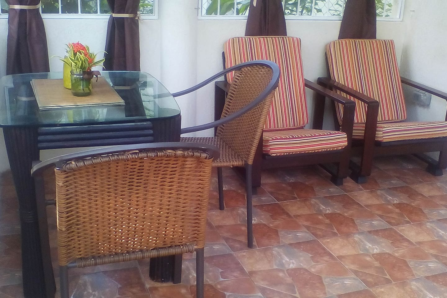 Enclosed patio with security bars, and insect screens. Sun loungers are also provided for relaxation and added comfort.