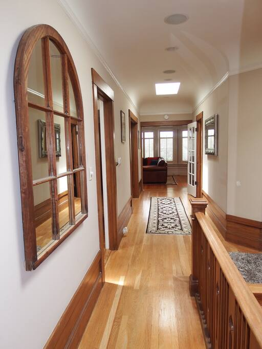 Hallway from bedrooms to living room, hardwood floors throughout