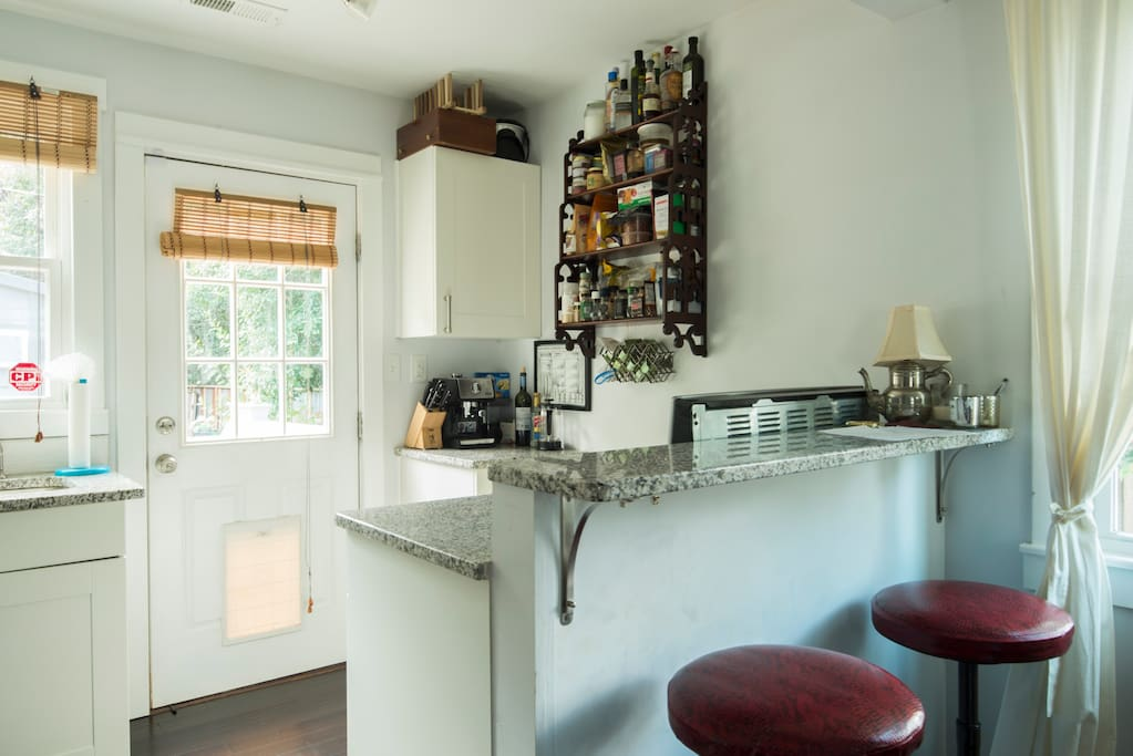 Kitchen with some basics.  Two seats at island. Nice view to backyard.