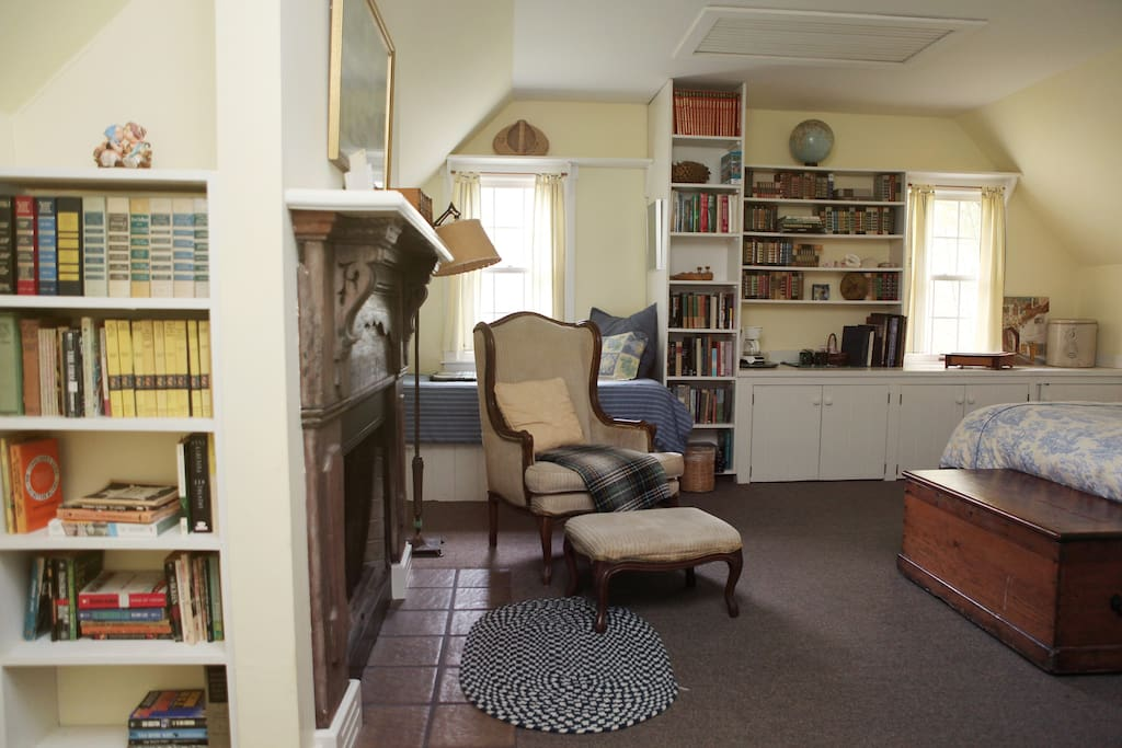 John's room with lots of books to read by the fireplace.