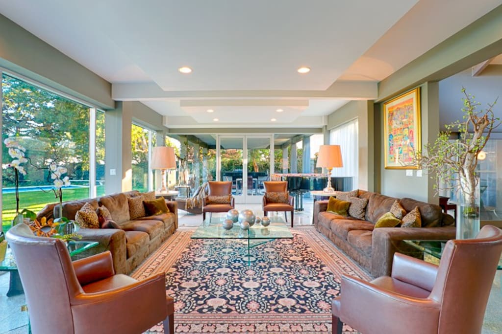 Back of this home has floor to ceiling windows. This is one of the two living rooms complete with a baby grand piano.
