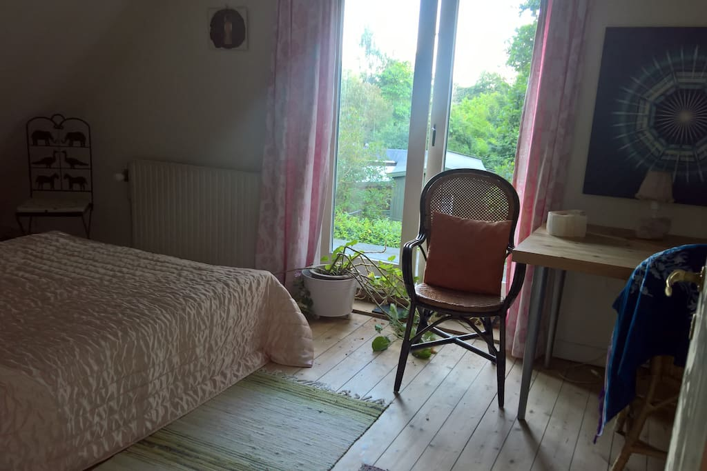 Bedroom with double bed and desk, green view.