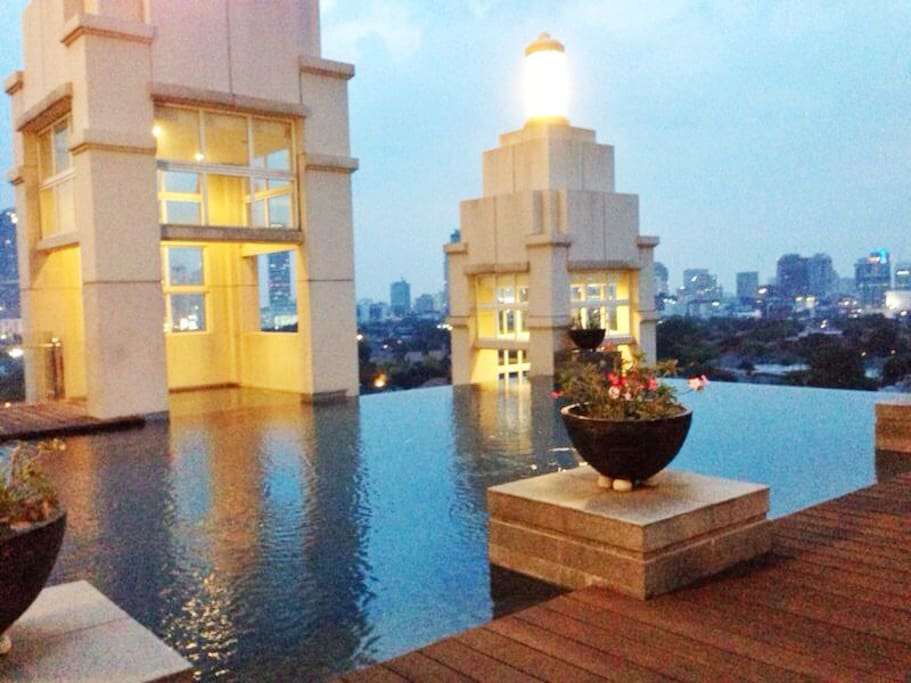 Outdoor rooftop infinity swimming pool at sunset with clear 360degrees view of Jakarta