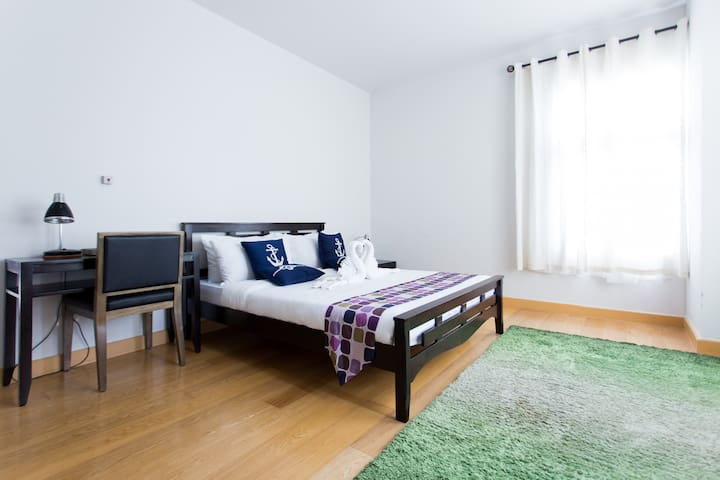 Spacious Master Bedroom with fitted wardrobes and en-suite bathroom/comfort room. Full-length windows with garden views