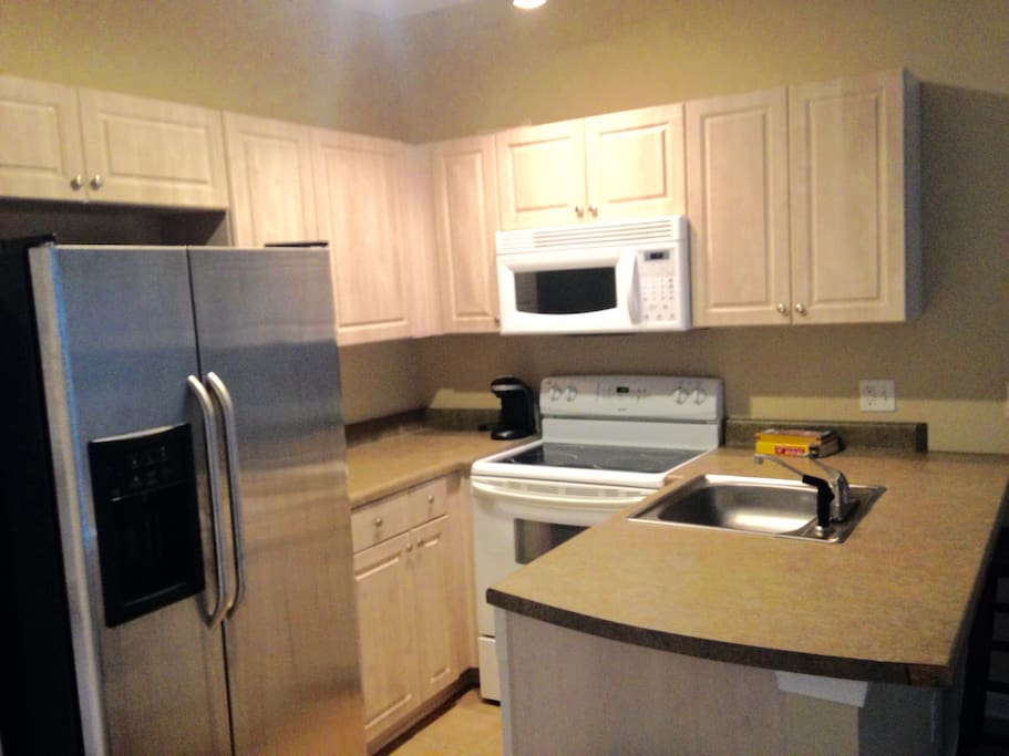 Kitchen with stainless steel frig and coffee maker.