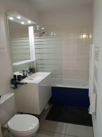 Salle de bain avec baignoire, lavabo, sèche serviette électrique et WC.