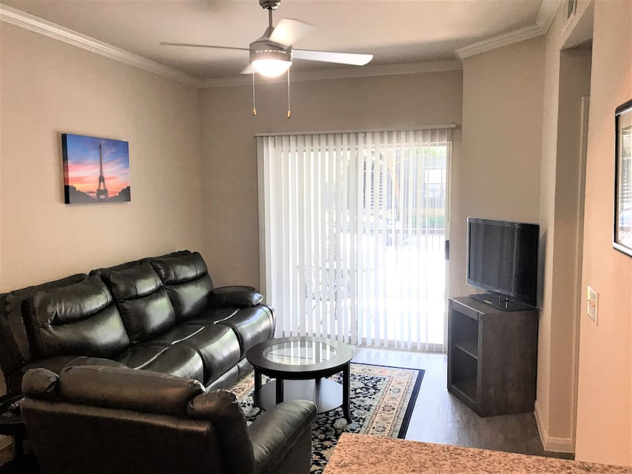 Living Room - Very spacious & includes TV with Netflix, AmazonTV, live TV & all premium movie channels (HBO, etc.) available through ATT App. New full-size comfy leather couch with electric reclinable seats, sofa chair, & high speed 50mbps Wifi.