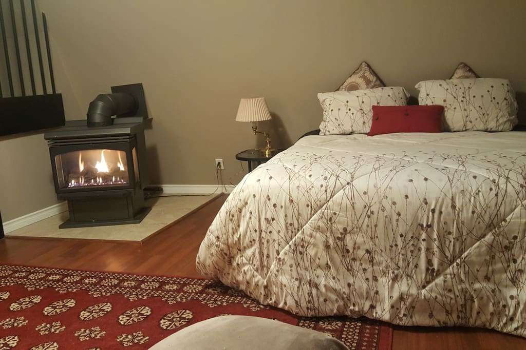 Queen size bed next to the gas fireplace.