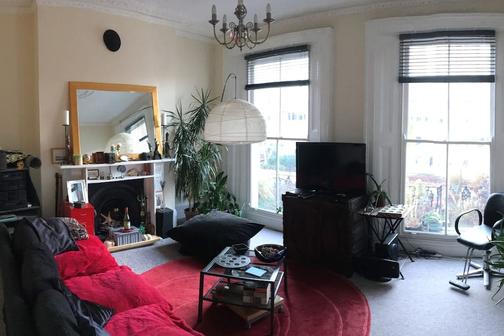 A beautiful sunny room with a balcony through the large windows.