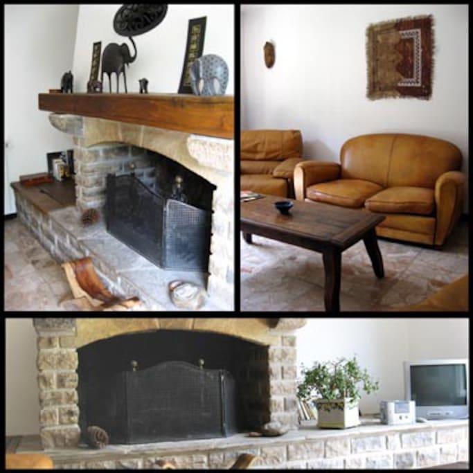 Le salon avec fauteuils cuir et cheminée.