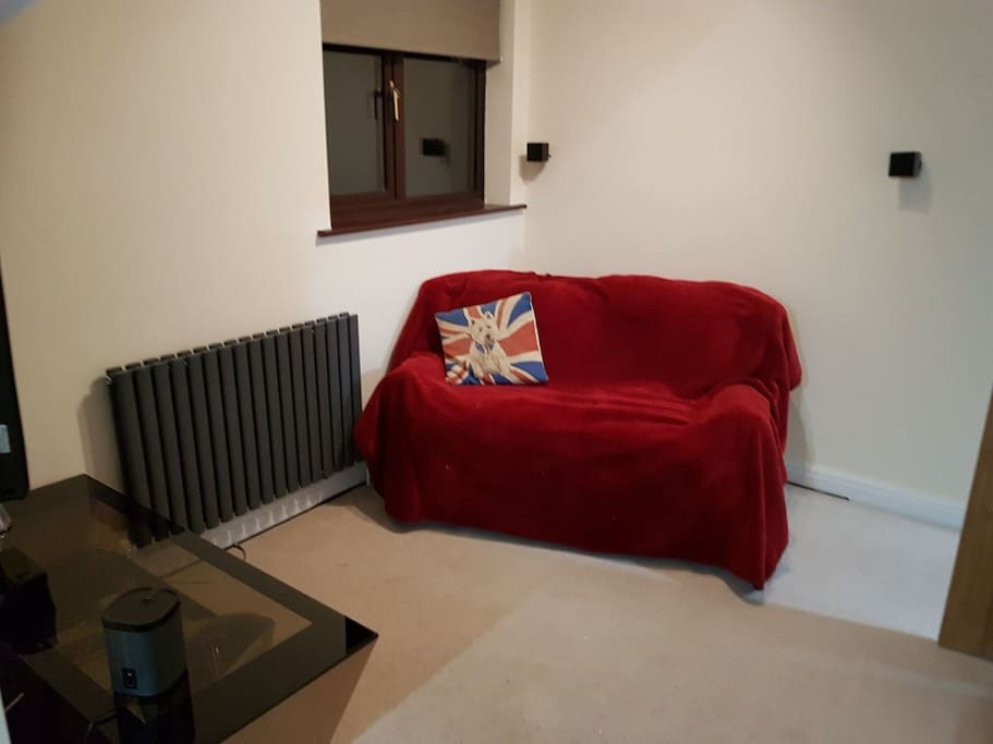 Two seater settee infront of large TV