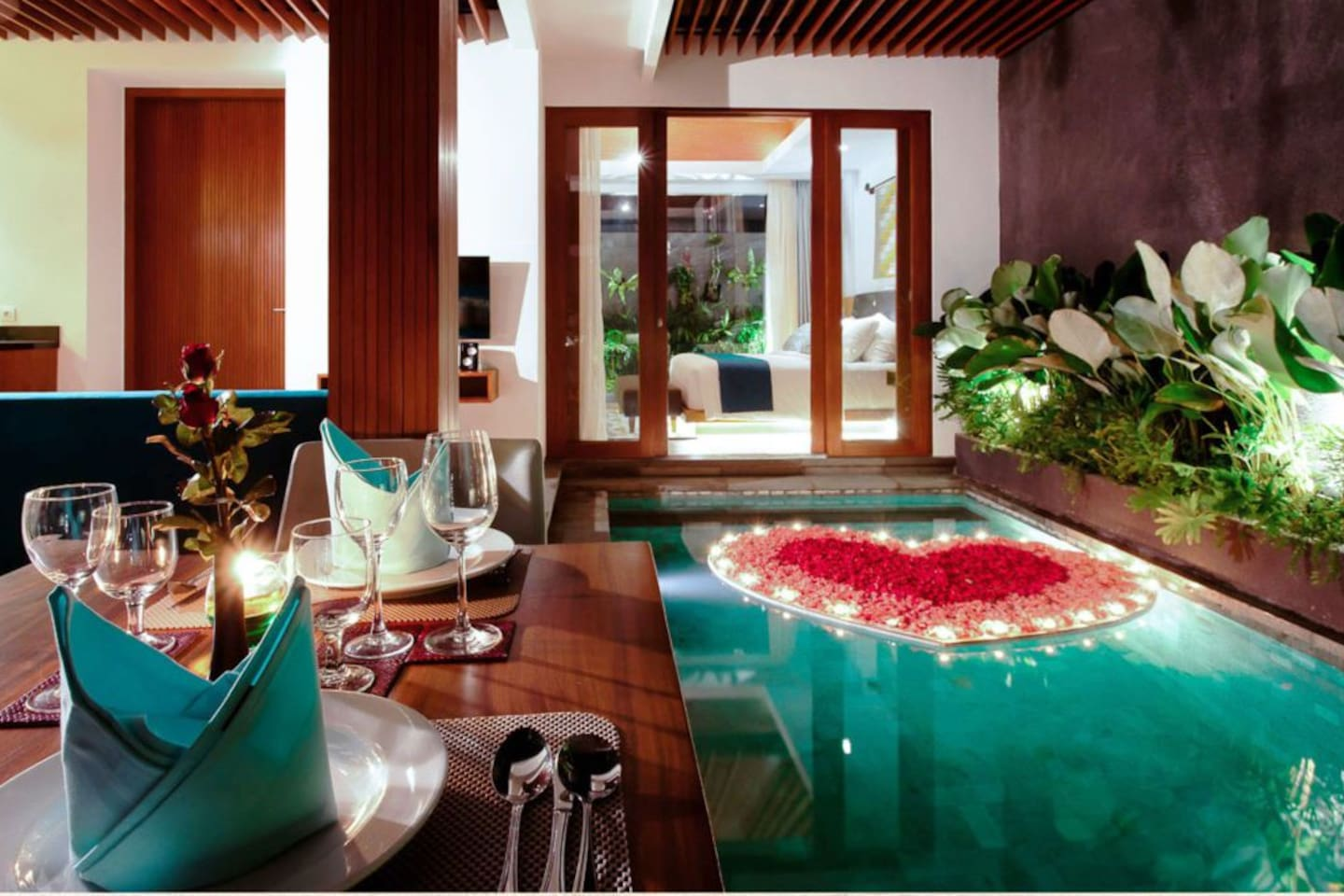 Romantic dinner setup with floating love at pool