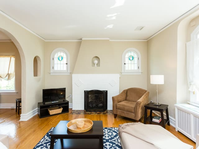 Multipurpose great room with  antique stained glass windows incorporating lounge with remote-controlled gas fireplace, study, and reading area