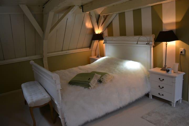 dit is het luxe witte bed in de witte kamer, die helemaal in de kleuren crème en mosgroen is uitgevoerd