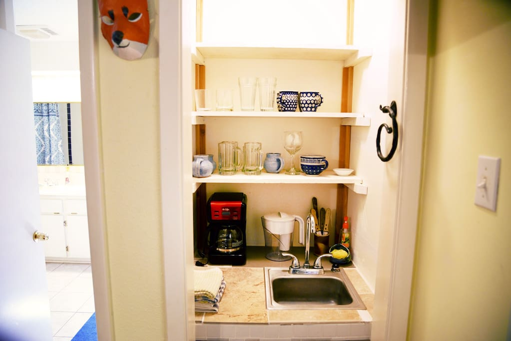 cozy kitchenette features coffee maker, sink, dishes, flatware, toaster oven, fridge freezer combo, blender, and microwave.