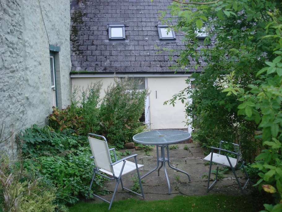 The enclosed back garden has steps leading up to a paved patio area with a table and four chairs ideal for a quiet drink or dining al fresco.