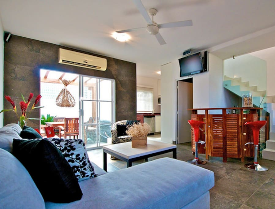 Sala de estar, cuenta con A/A, Televisión con señal satelital, reproductor de DVD home theater, medio baño, cantina, comedor y cocina al fondo.