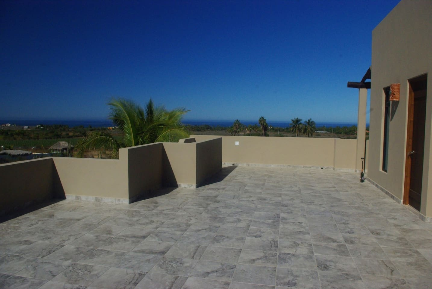 Partial view of the patio and Pacific Ocean where the stairs come up for the front door entrance to the apartment on the right!