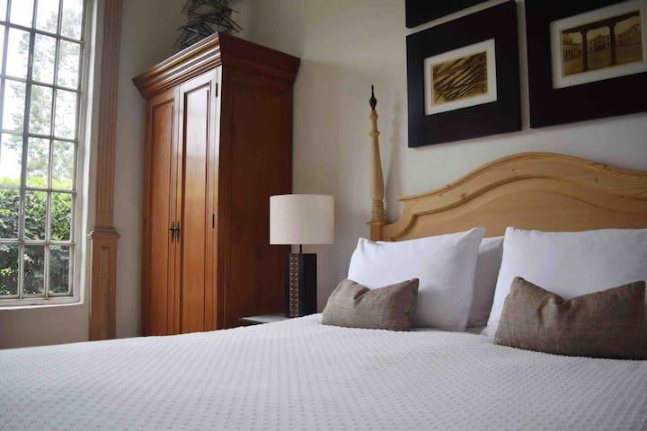 Dormitorio principal. Cama Queen y TV con cable. Ventanas amplias con vista al jardín.