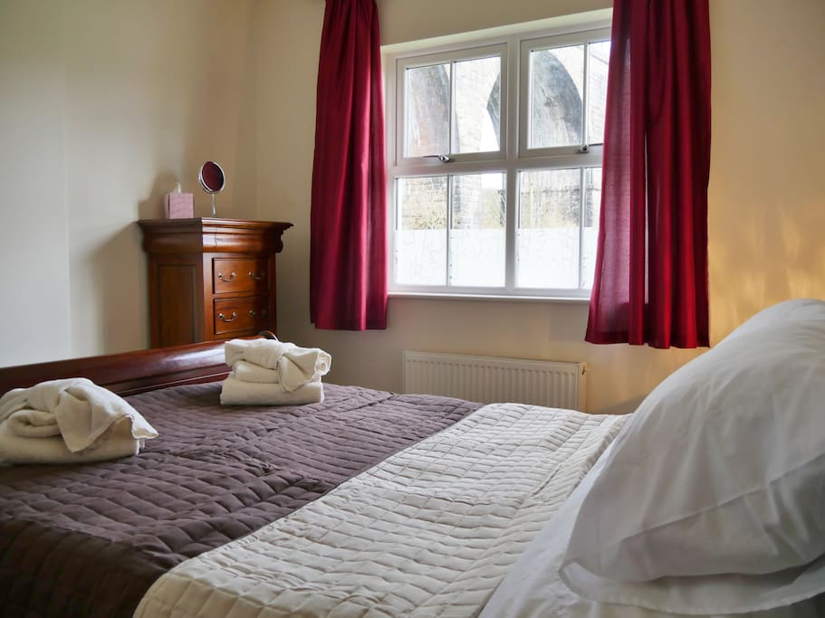 Master bedroom with king size sleigh bed and sleigh furniture. Views of viaduct