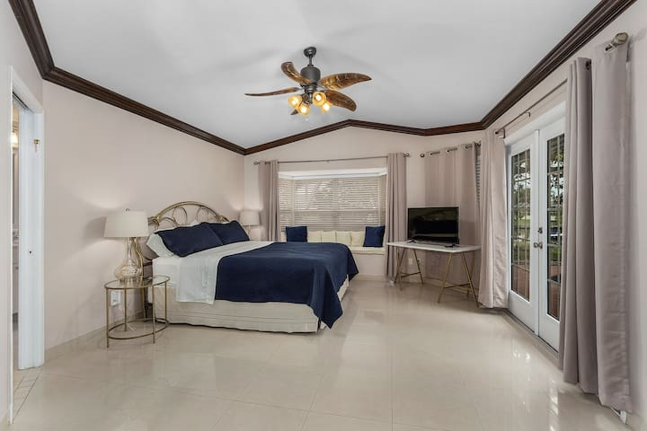 Master Bedroom with king sized bed and french doors that go to the pool