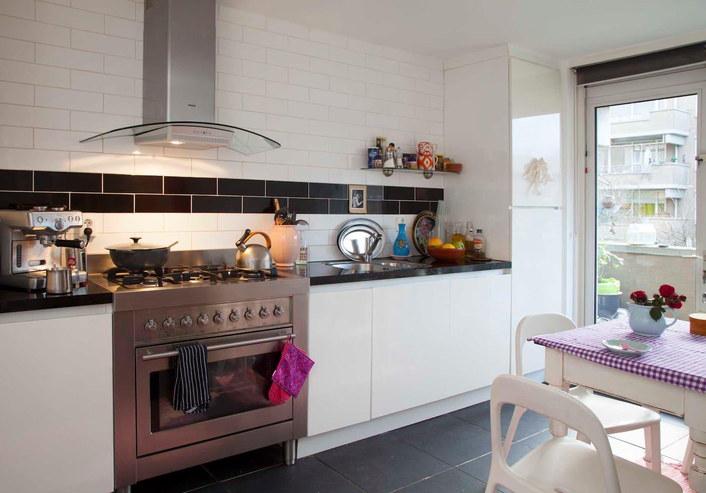 Spacious kitchen with espresso machine, dishwasher, fridge, etc- opens to a small balcony.