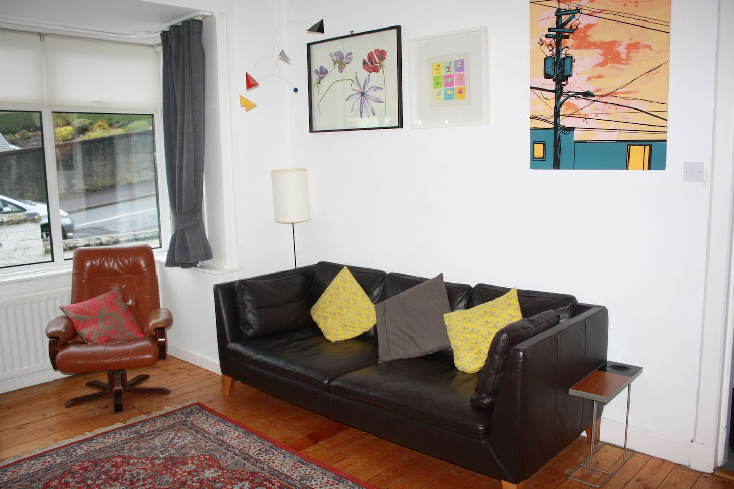 Bright & spacious front living room with original artwork and wooden floors.