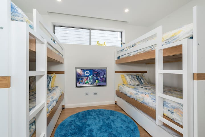 Third bedroom with two sets of bunk beds with trundles and a recessed television with connections for electronic games