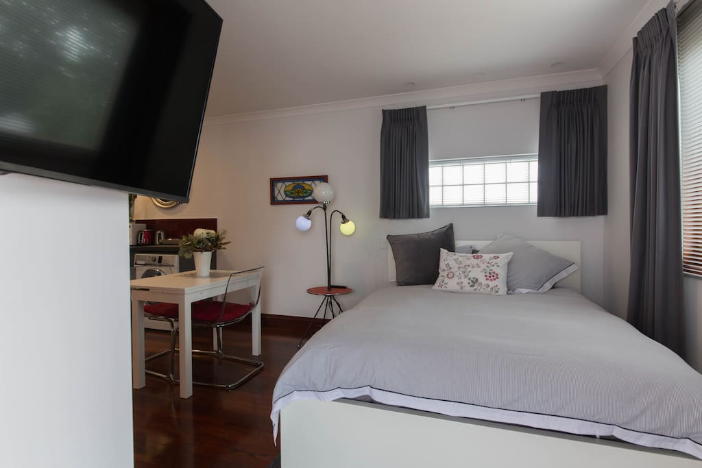 Wall-mounted TV swivels to allow viewing from bed