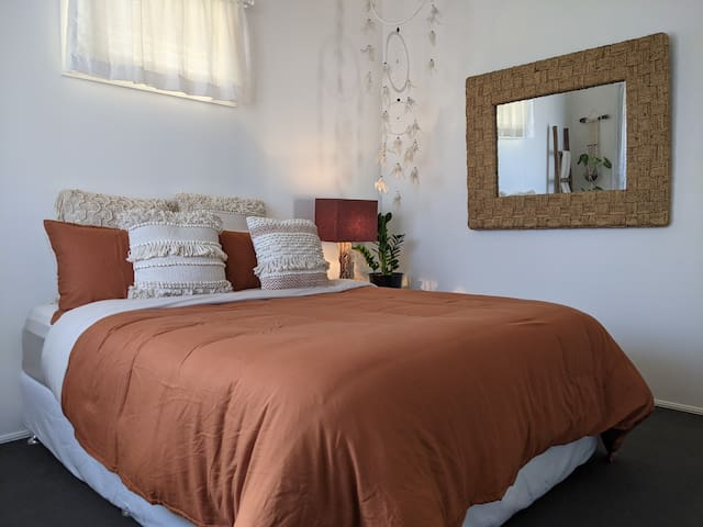 Spacious bedroom with a comfortable queen bed, ceiling fan and aircon.