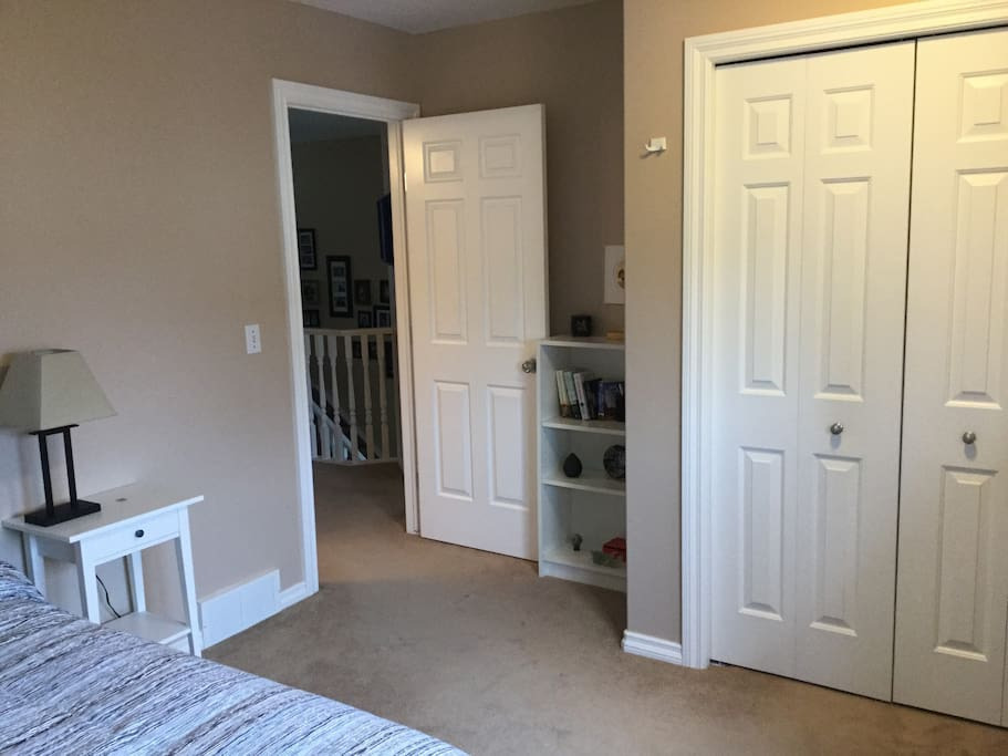 a large closet with hangers and a choice of bathrobes for your use