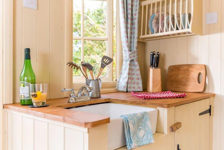 Kitchenette with butler sink, full-sized fridge, pans, crockery, picnic stove...