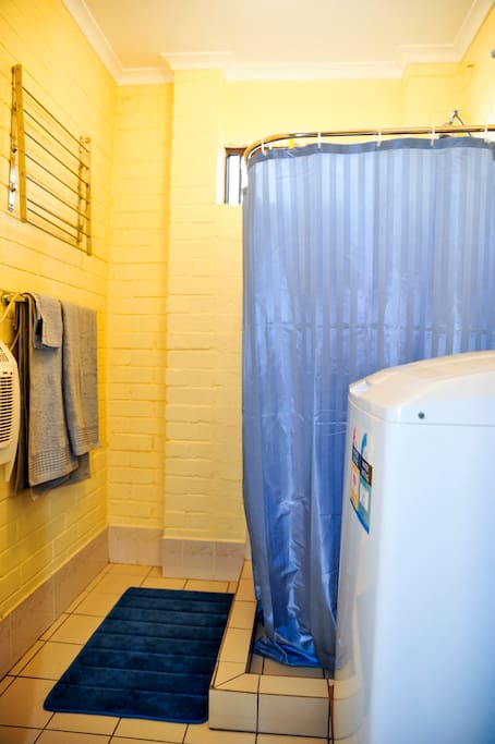 Bathroom contains a shower, additional wall heater and washing machine.