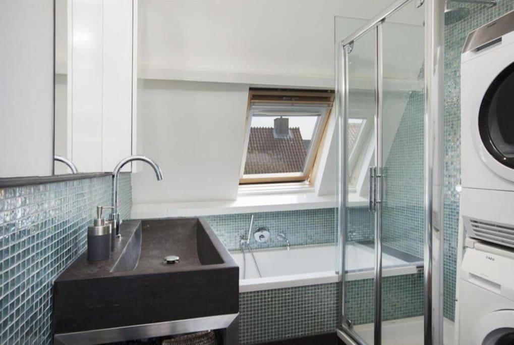 Bathroom with shower, bathtub, Miele washing machine and dryer