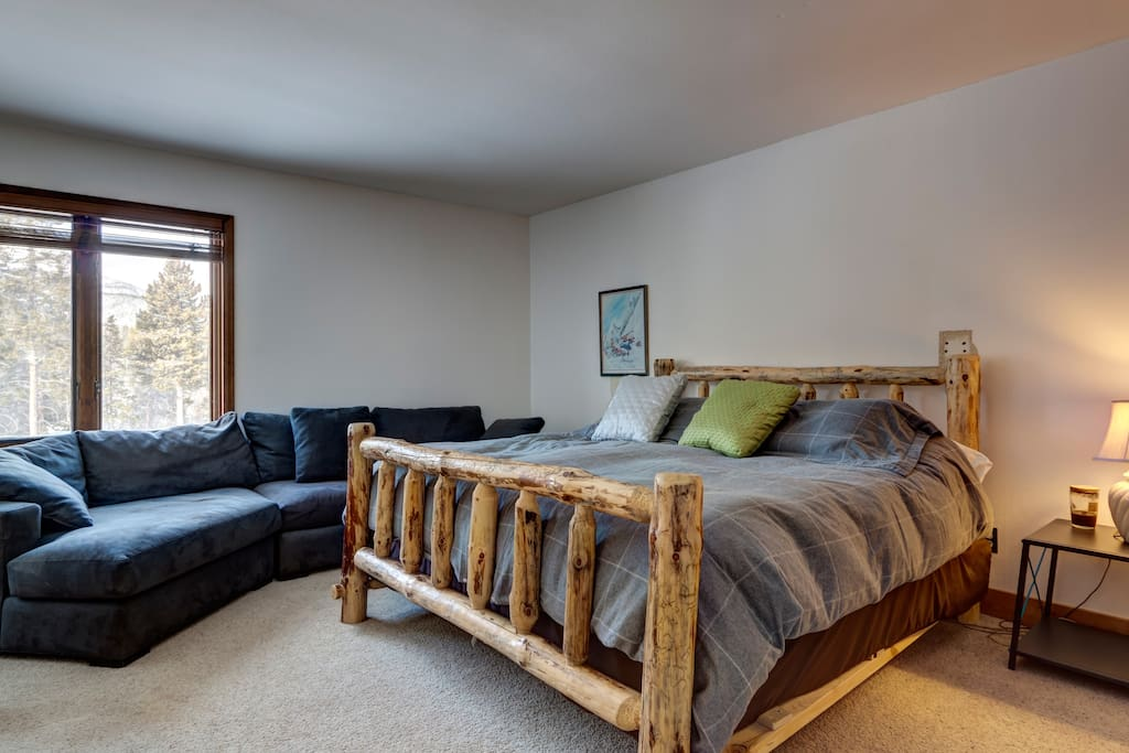 Master Bedroom with king bed, mountain views, plush feather couch, and en-suite bathroom.