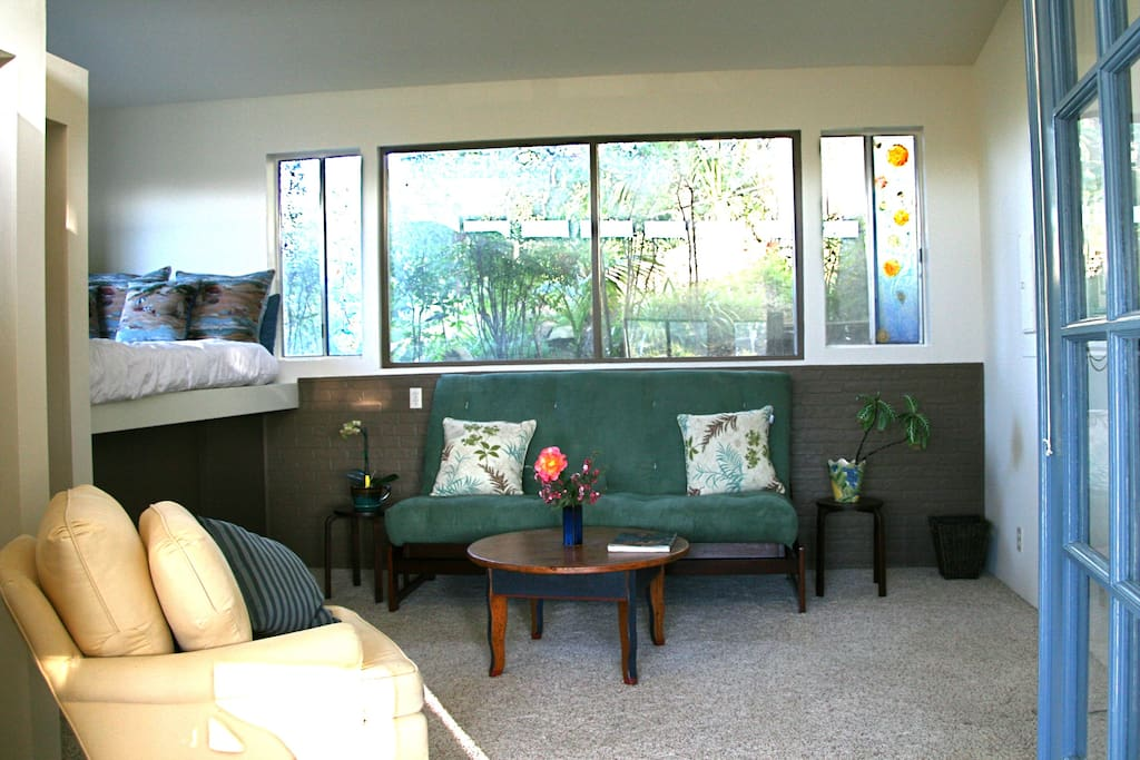 Sitting room with double loft bed on left, and green futon sofa/double bed.