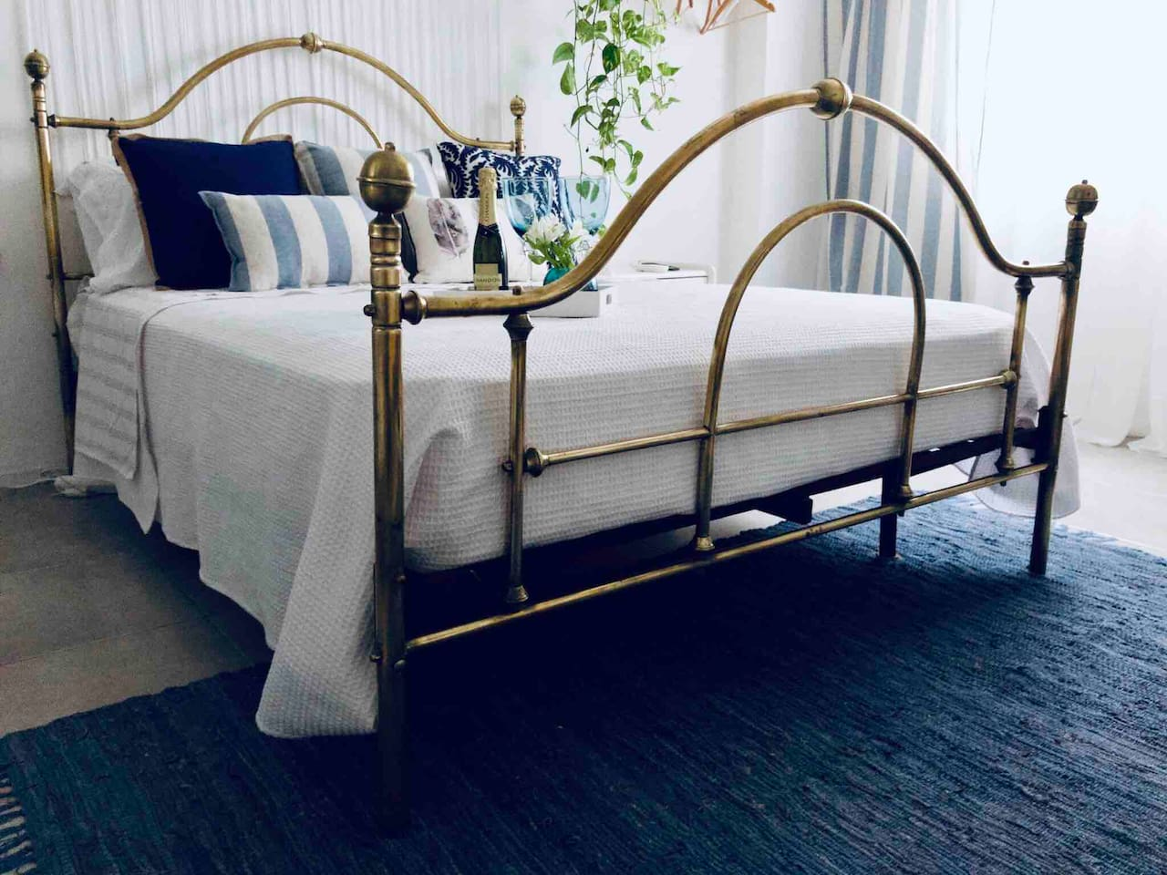 Bronze made queen size bed. The cushions has been designed and made by the apartment host, creating an authentic and unique apartment decoration.
