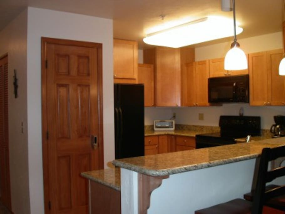 Kitchen with Granite Counter GE Profile Appliances and 4 barstools