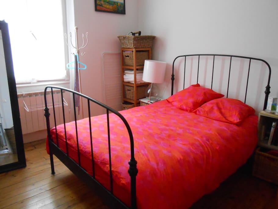 un grand lit, matelas confortable, donnant sur le jardin