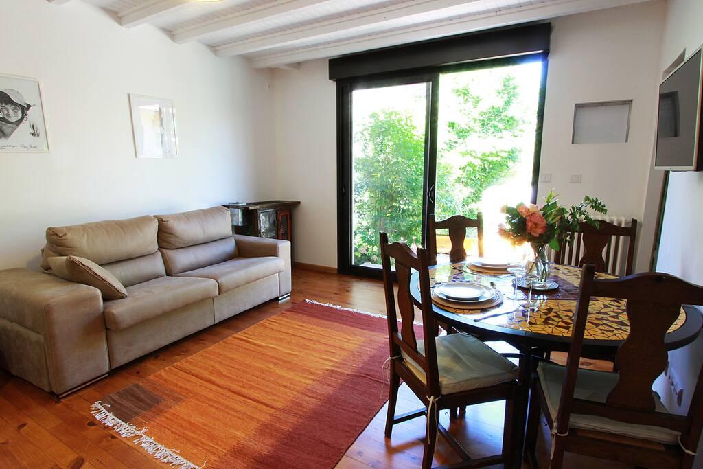 Cote salon , salle à manger:  . Une baie vitrée ouvre sur une grande terrasse au milieu du jardin qui permet de se détendre à la belle saison et de prendre ses repas dehors.